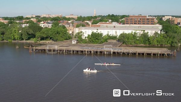 A crew team rowing along the Alexandria, VA waterfront with chase boat