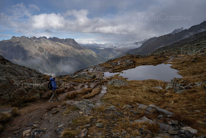A young woman hikes along a rocky mountaintop trail in the French Alps with an epic view.