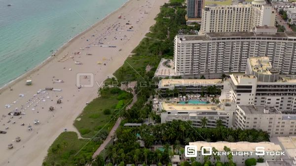 Aerial tilt down to Miami Beach old deco hotel swimming pool
