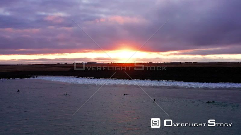 A Pull Back of Surfers Paddling Out at Sunset in Iceland.