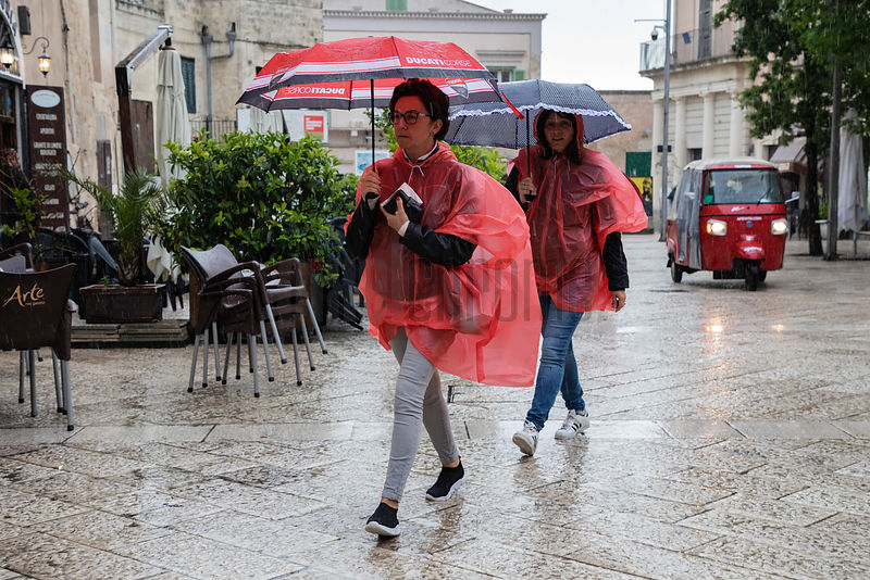 A Couple in Red Ponchos Walking in the Rain