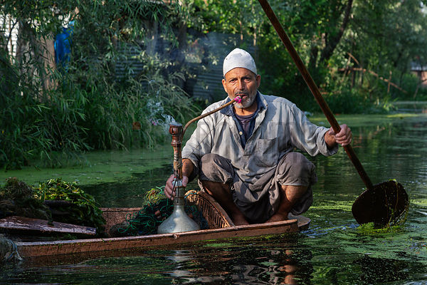 Fisherman Smoking a Hookah While Paddling His Canoe
