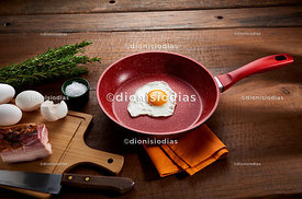 Fried egg in red frying pan with preparation next to it