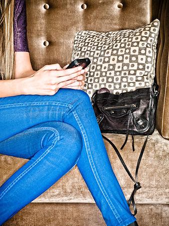 image of blonde female in blue jeans sitting on bankett with clutch, texting on a smart phone