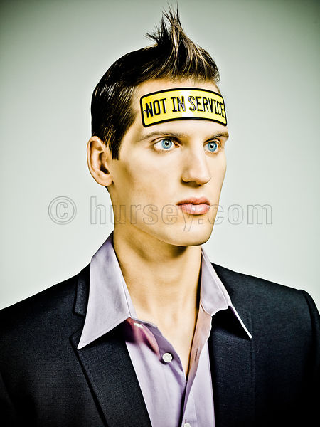 "male fashion model looking ""vacant"" with a tin plate bolted to his head saying ""Not In Service"""