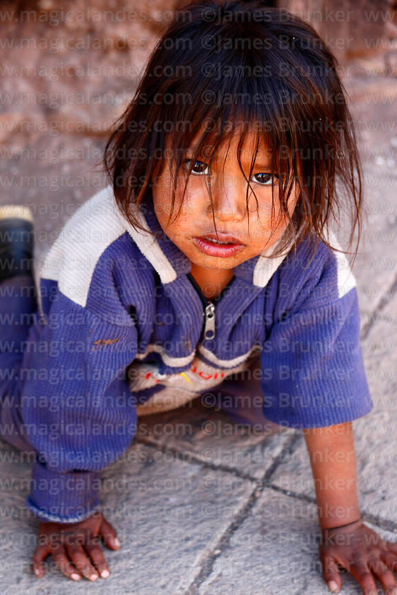Young Quechua girl crawling on pavement, Pisac, Sacred Valley, Peru