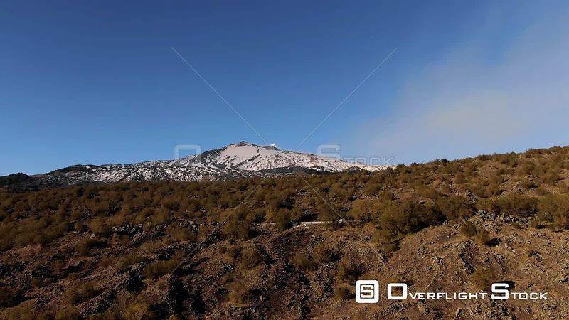 Aerial view of mount Etna with lava rock and shrubs