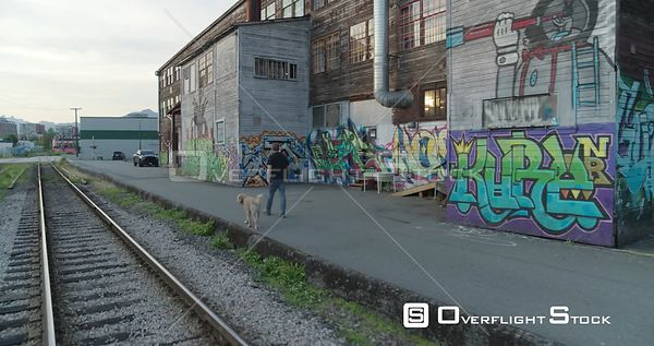 Old Wood Sided Warehouse with Graffiti at Sunset. Parker Street Studios, Vancouver, BC, Canada. Dog Walker