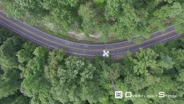 Drone in Flight Over a Winding Road in Forest