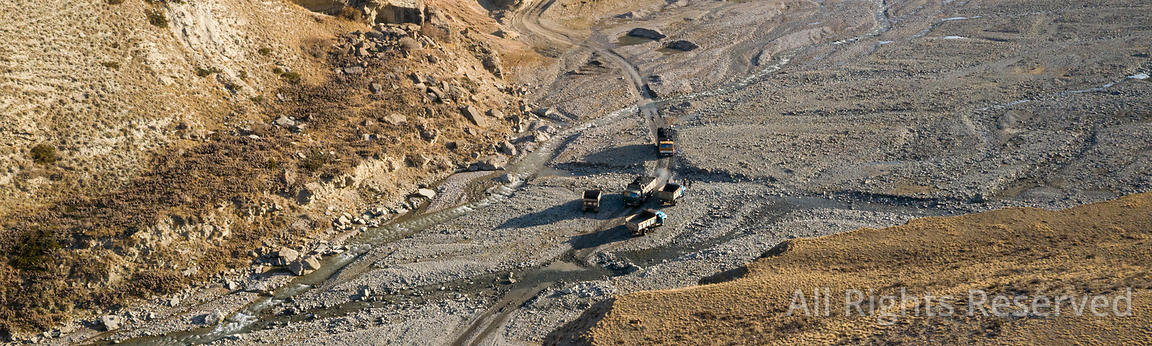 Aerial Image Showing Trucks Traffic Coming from the Coal Mine Crossing the River Bed in the Arpa Valley of Kyrgyzstan