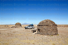 Toyota Land Cruiser driving past houses made from flat, sedimentary, stromatolite rocks in a Chipaya community, Oruro Departm...