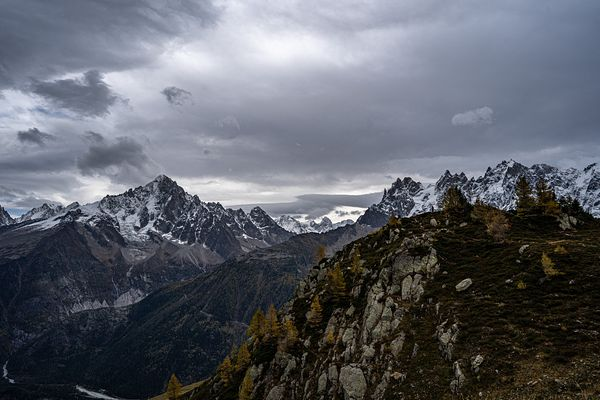Climbers in the distance reach a mountain peak in the French Alps. Photo by Jason Tinacci