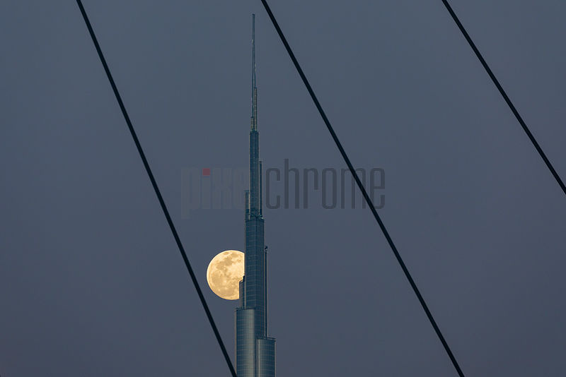 Super Moon behind Burj Kalifa through the cable stays of the Tolerance Bridge
