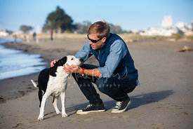 Man on beach holding and petting his dog