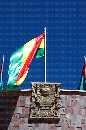 Modern copy of Viracocha / Wiracocha figure on top of facade of town hall and Bolivian national flag for festival, Tiwanaku, ...