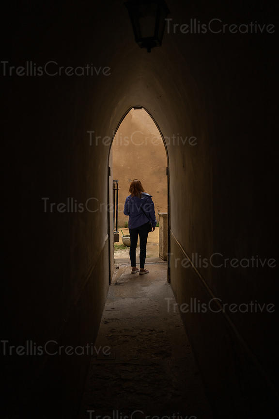 A young woman walks inside the famous Traboules or secret passageways of Lyon, France