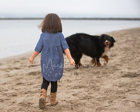 Little Girl Walking Toward Dog on Beach
