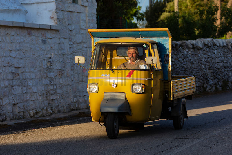 Local Farmer Rides in an Ape 3-wheeled Vehicle