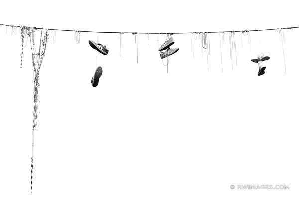 SHOES AND MARDI GRAS BEADS HANGING ON POWER LINE FRENCH QUARTER NEW ORLEANS LOUISIANA BLACK AND WHITE