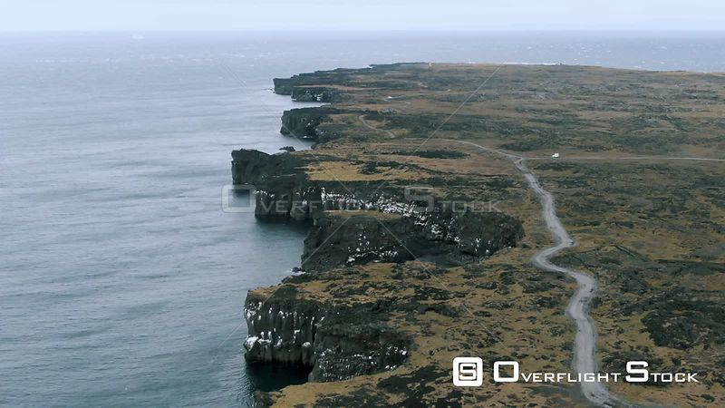 A Black Rocky Coastline Revealing a Lighthouse in West Iceland