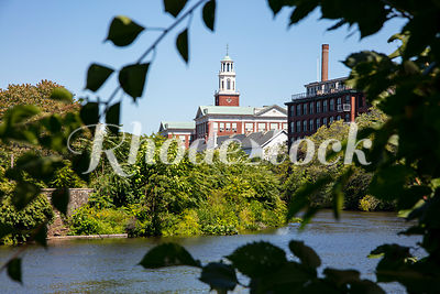View Through Trees Across River of Historic Red School Building