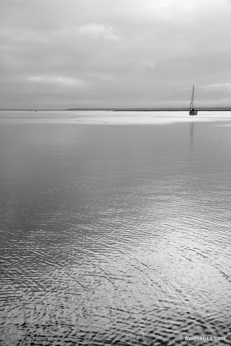 LONE SAILBOAT CUMBERLAND ISLAND SOUND CUMBERLAND ISLAND GEORGIA BLACK AND WHITE VERTICAL