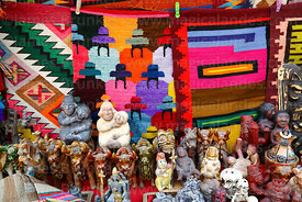 Bull and erotic statues and weavings for sale outside shop, Ollantaytambo, Sacred Valley, Peru