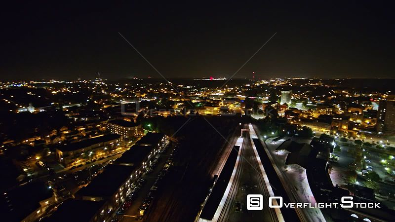 North Carolina Greensboro Aerial Panning around moving train with nighttime cityscape backdrop