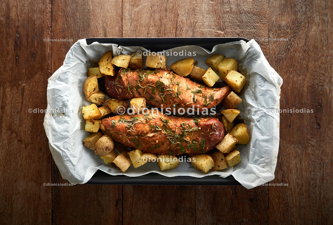 Pork tenderloin in a baking pan with potatoes.