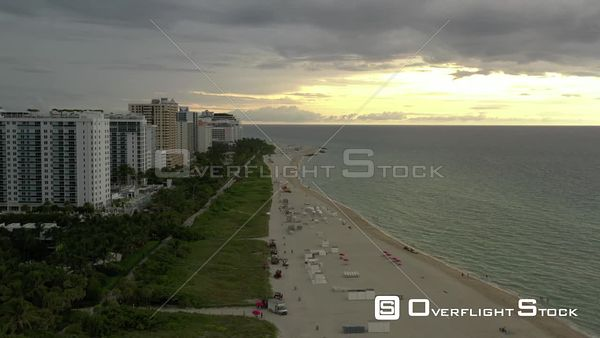 Aerial Miami Beach bright sun through clouds over ocean 4k 60p