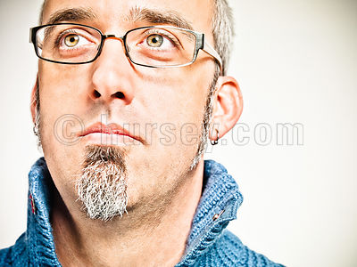 portrait of mael with salt and pepper hair, glasses, and a goatee in a blue sweater shot on a white background.