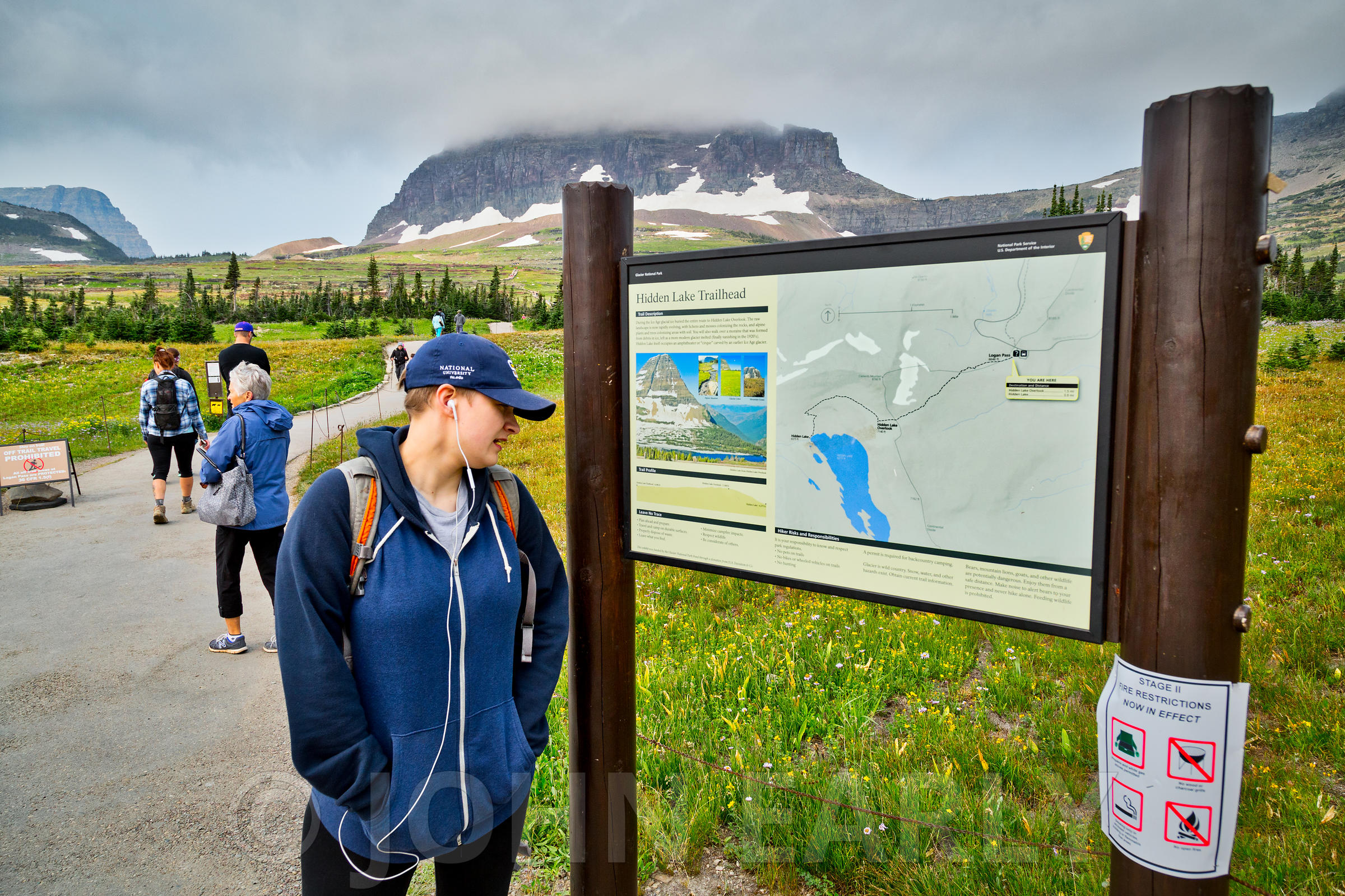 Teenager reading visitor info map at Logan Pass.