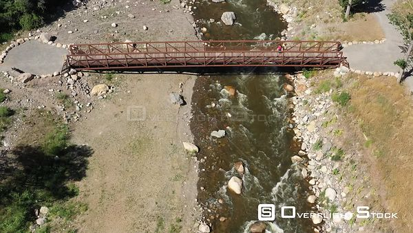 Person on a bridge over a trout stream, Estes Park, Colorado, USA