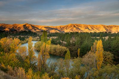 Sunset lights up the hills above the Clutha River which flows out of Lake Wanaka.