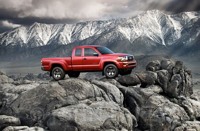 2007 Toyota Tacoma positioned on rocks with snowy mountains in the background
