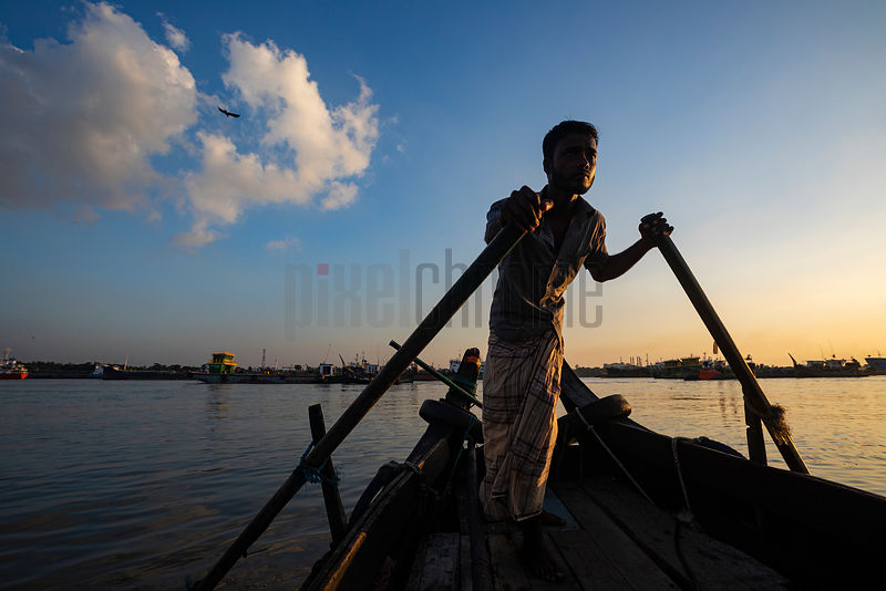 A Boatman Paddles his Noakhali on the Karnaphuli River at Sunset
