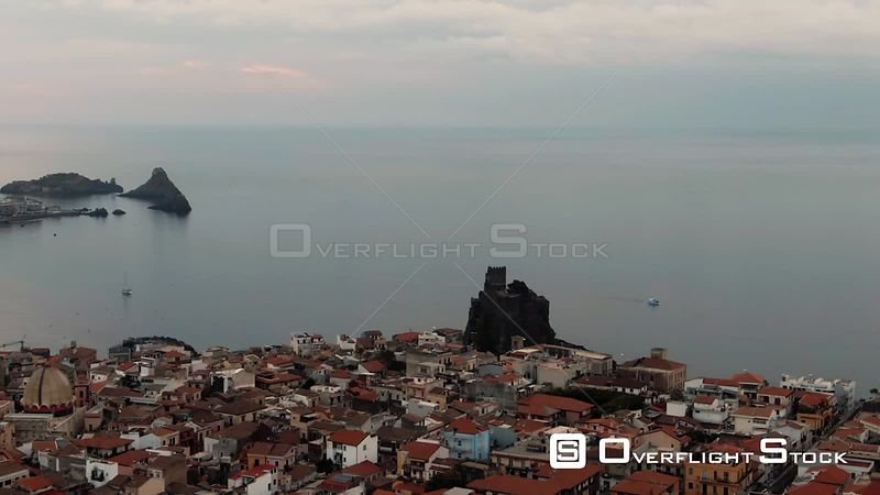 Aerial dolly view of the fishing village of Aci Castello in East Sicily with the norman castle. Italy