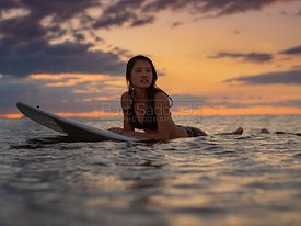 Surfer Girl on surfboard at sunset