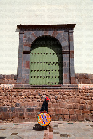 Man carrying drum past Inca wall and Santa Ana church door, Cusco, Peru