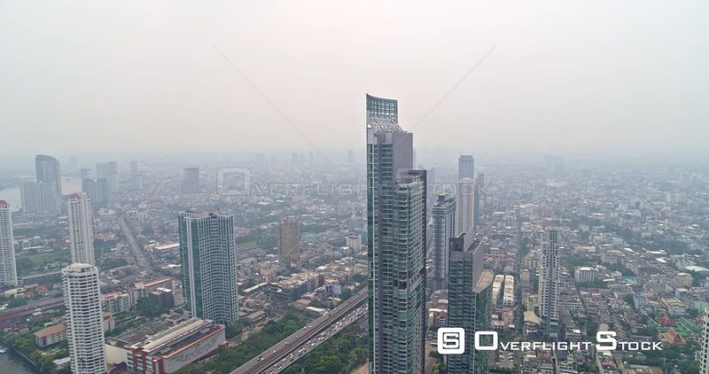Thailand Bangkok Aerial Panning around resident tower with cityscape and river views