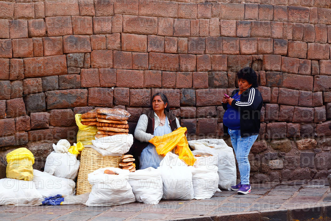 Woman selling pan chuta / bread from Oropesa in front of Inca stone wall, Cusco, Peru