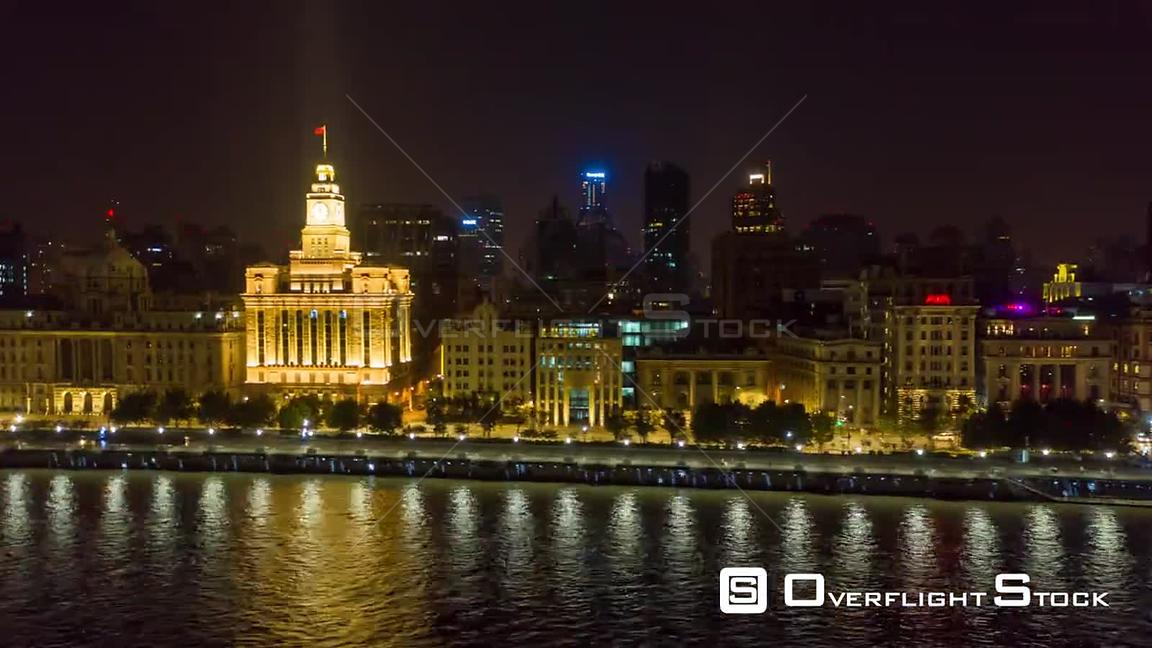 China Shanghai Aerial Hyperlapse flying low over Huangpu river looking toward waterfront promenade at night