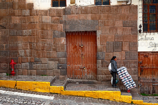 Woman pushing trolley of packs of toilet paper past an Inca stone wall, Cusco, Peru
