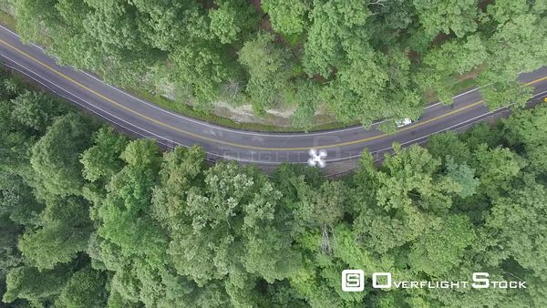 Car Tracking on a Road with a Drone in Flight Over a Winding Road in Forest