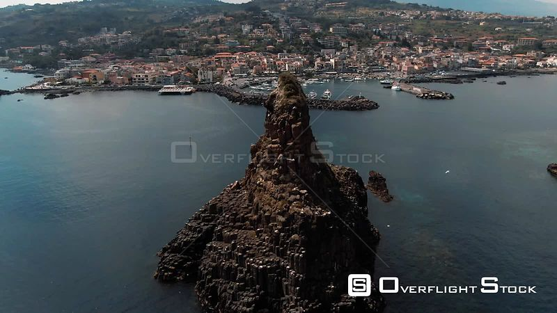 Aerial orbiting view of the faraglioni and the fishing village of Acitrezza. Italy