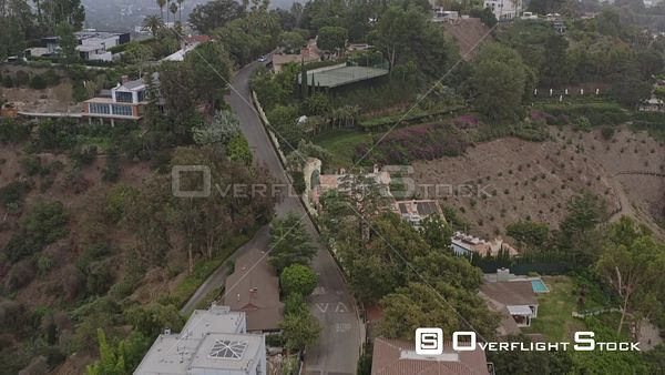 Los Angeles Flying birdseye low over hillside mansion residential neighborhood