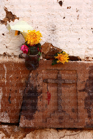 Carved stone cross above an Andean cross or chakana on wall and floral offerings, San Blas district, Cusco, Peru