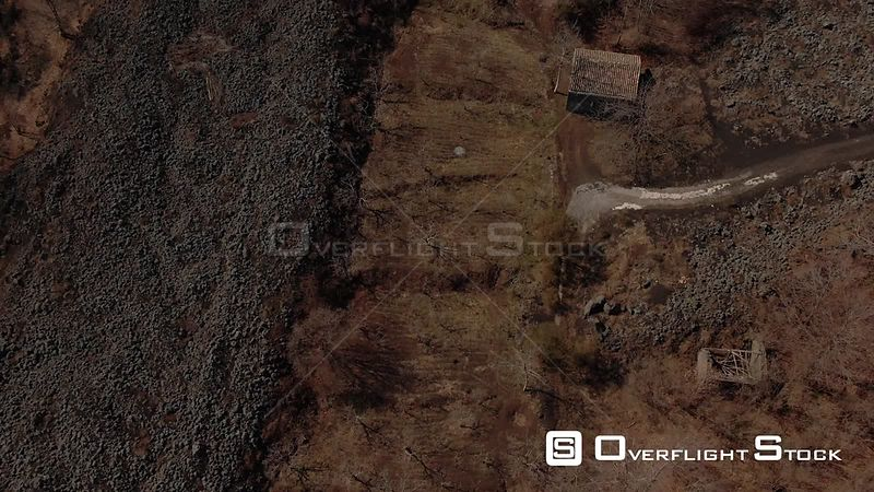 Aerial tilt up view over lava rock, trees and shrubs revealing mount Etna in Sicily. Italy