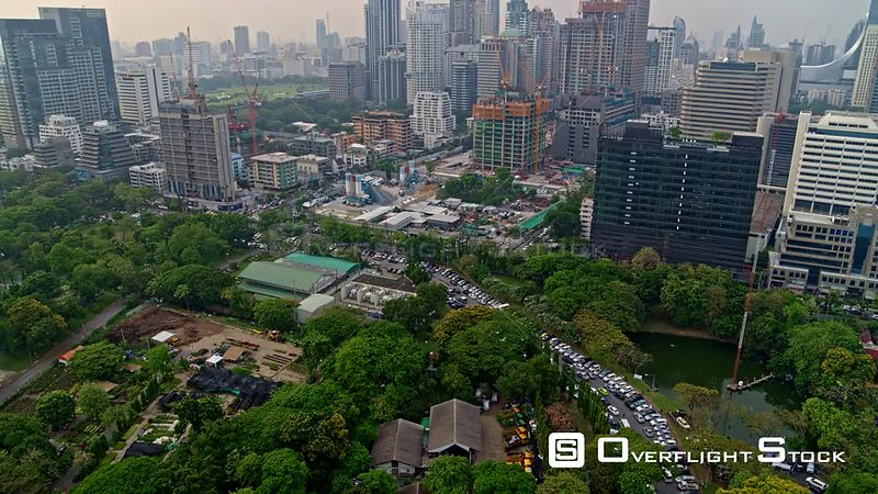 Thailand Bangkok Aerial Flying in low, birdseye view of Lumpini Park edge and cityscape construction