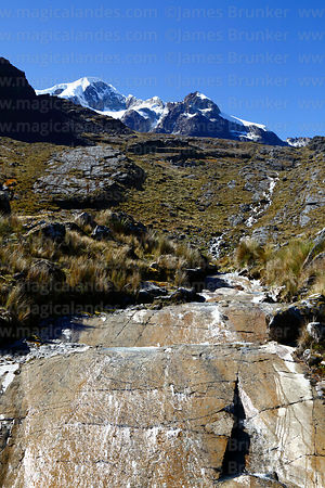 Stream flowing over rock slab with glacial striations, Mt Ancohuma in background, Bolivia